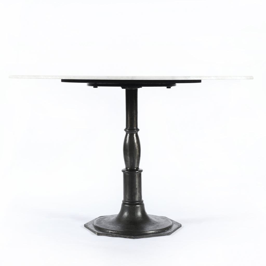 French industrial meets dining table. Beautifully detailed, 8-sided cast iron pedestal supports a dramatic white marble top with a bull-nosed edge.