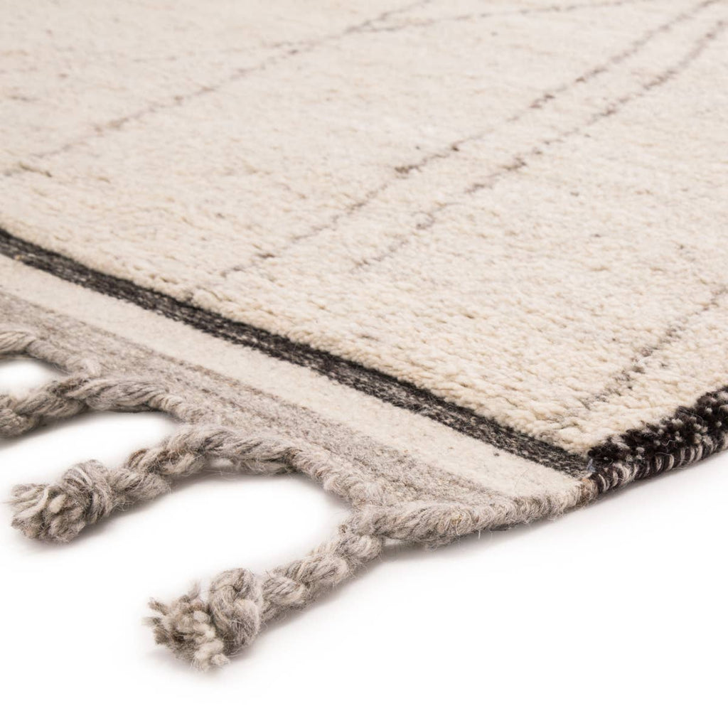 Simple and yet beautifully textured for a global vibe, the Mina collection features hand-crafted Moroccan designs. The hand-knotted Danforth area rug boasts an ivory, black, and gray colorway, authentic and shaggy wool pile, large braided tassels, and a classic tribal trellis for the perfect grounding piece in any modern space.