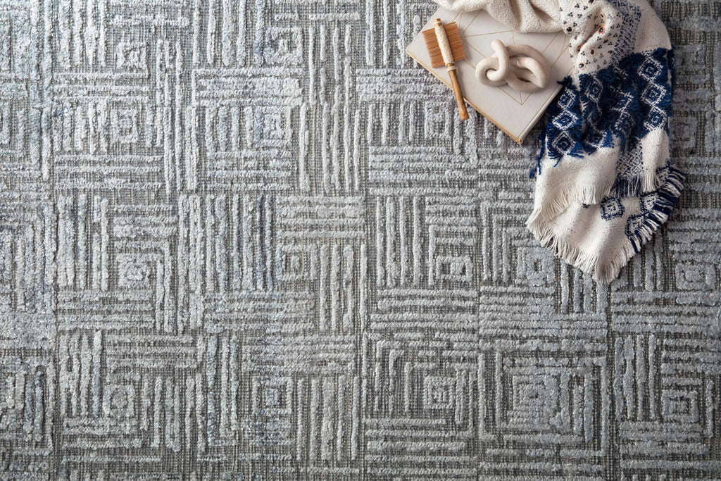 Featuring tone on tone geometric patterns, the Lana Denim Area Rug is hand-knotted of wool, viscose and cotton. Crafted in India, the refined high-low pile is a testament to the dedication of craftsmanship required to create each rug. This would go great in a living room, kitchen, or other medium to high-traffic areas.