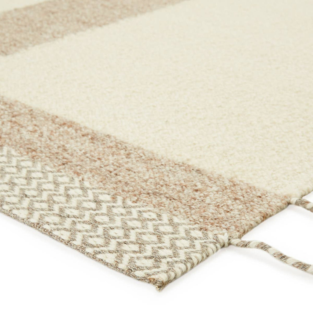 The Nazca Calva Area Rug, or NAZ01, by Jaipur is hand-loomed of texture-rich wool. The Calva area rug boasts a neutral light tan and cream colorway, and the diamond lattice border with braided tassel details add a beautiful, unique touch. This is a perfect rug for a living room, bedroom, or other high-traffic areas.