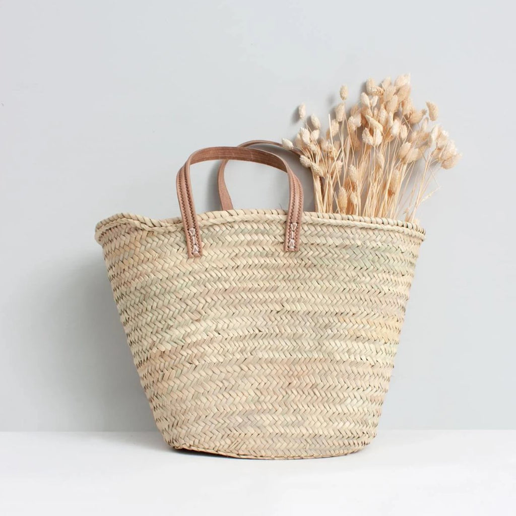 The Parisienne Basket with natural leather handles, is a classic handwoven market basket made from sustainable palm leaf and handmade leather.  Also available with tan leather handles in extra large for a great home storage solution.