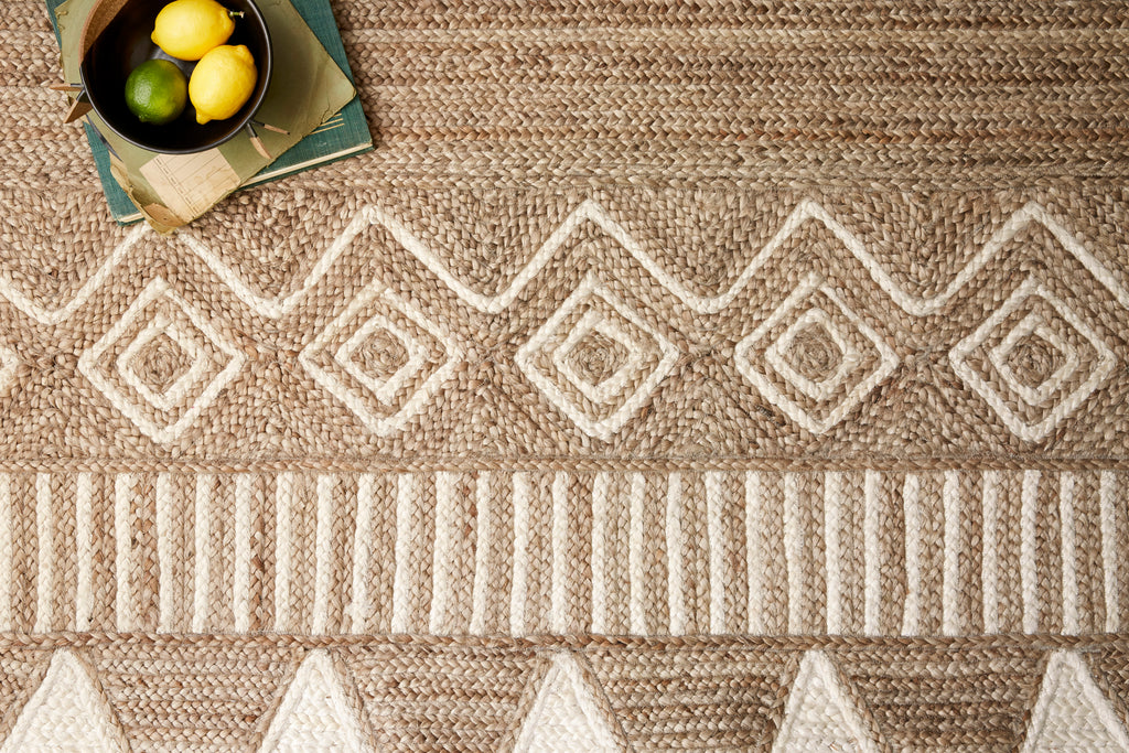 Crafted by Loloi for ED Ellen DeGeneres, the Redondo Natural / Ivory Area Rug by ED, or REO-01 ED, features a display of geometric and tribal-inspired designs. Braided of 100% jute in India, Redondo is modernized by a rich color palette for a warm and inviting ambiance underfoot.