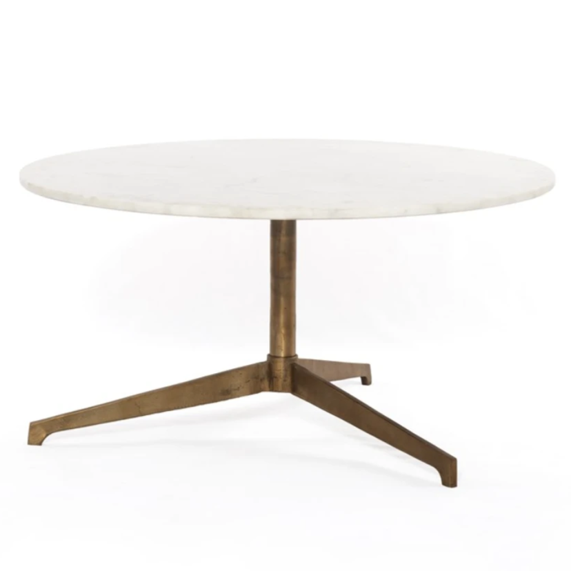 Simple, sophisticated style. The Helen Round Coffee Table has a slim tripod base of raw brass supports a rounded tabletop of polished white marble. Petite scale perfect for smaller spaces or rooms with a sectional.