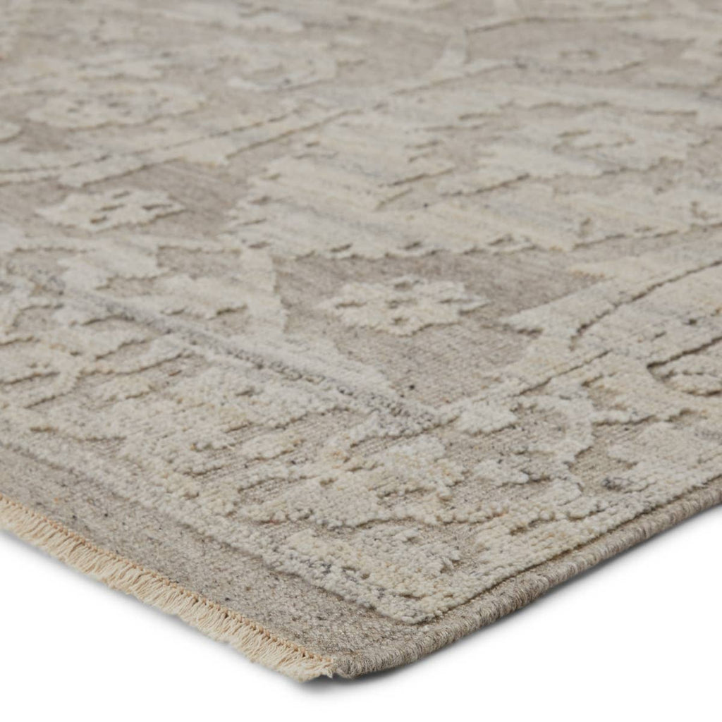 The Sonnette Ayres Area Rug by Jaipur Living, or SNN03, boasts a neutral palette of light taupe and gray that creates beautiful dimension among the brocade design. This hand-knotted wool rug features fringe trimmed details for a touch of global charm. A gorgeous choice for your bedroom or other medium traffic areas.