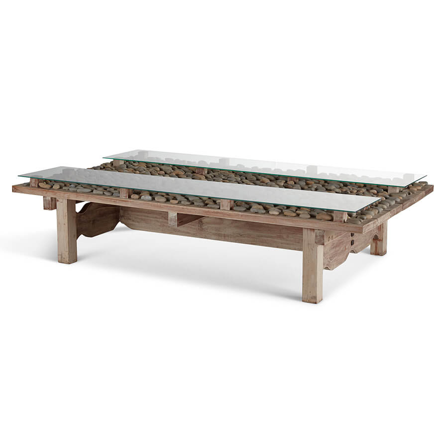 The base of this unique table is made of Cedro Macho wood that is locally harvested in Nicaragua. The wood has a natural whitewash finish. The stones are collected on the coast and affixed to the top by hand. The two glass panels are included with light assembly required.
