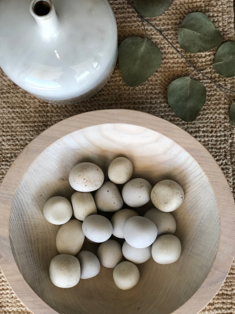 "Natural and smooth, these soft stone pebbles make a gorgeous addition to any scene. Each stone is roughly 1"" with each cotton muslin bag containing at least 16 pebbles. These stones are perfect in a marble bowl, wooden bowl, laid out as decoration on a table, at the bottom of a flower vase, or anywhere else!"