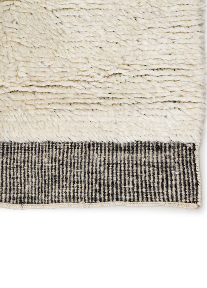 The Tala collection of hand-knotted rugs brings a new sense of luxury and comfort to the contemporary home. The Ephesus rug makes a modern Moroccan statement, showcasing an asymmetrical geometric motif and a striped flatweave border. An ultra-plush pile of soft wool highlights the unique design of this ivory and black accent.  Hand-Knotted 100% Wool TAL06