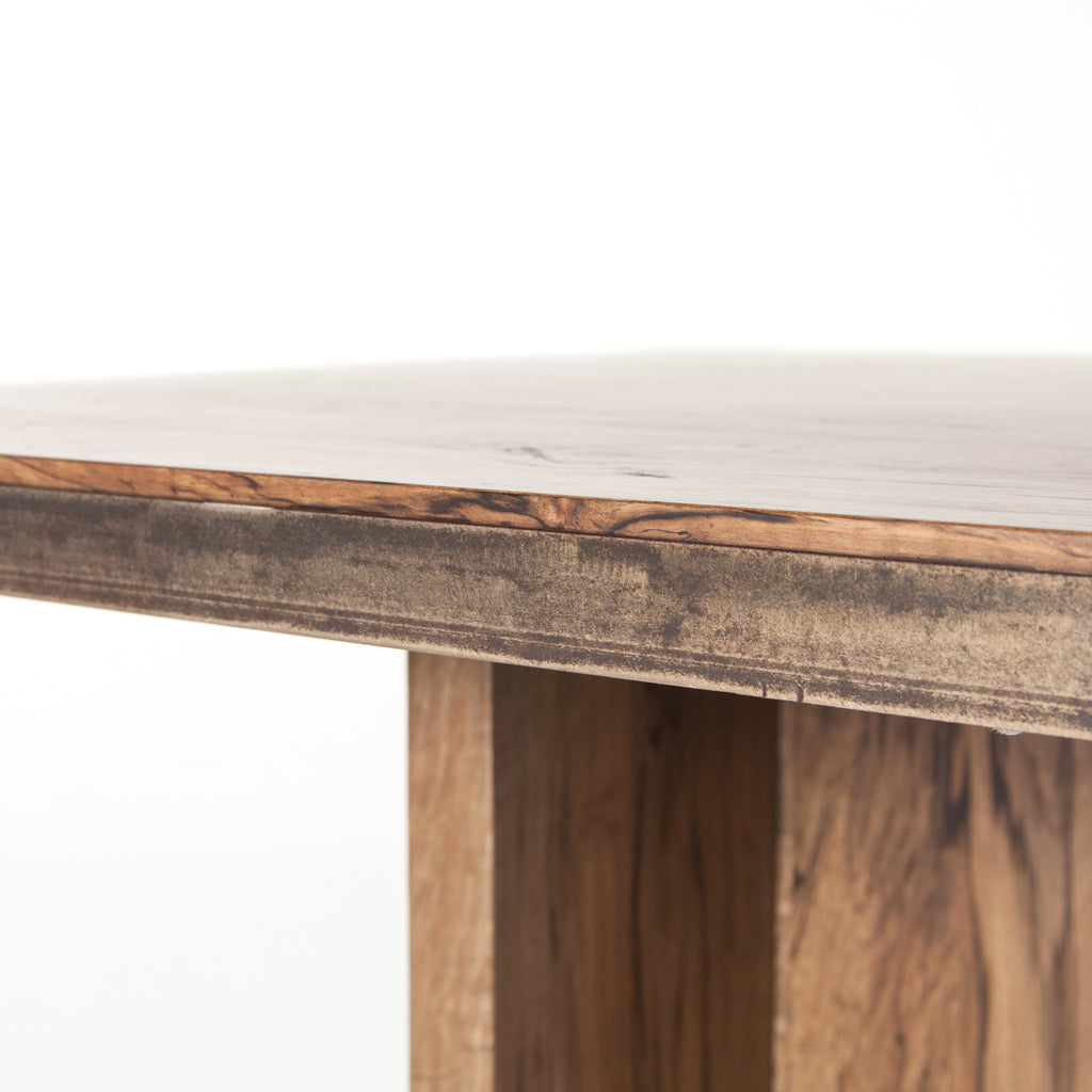 Iron strapping with a brushed gold finish adds a rustic, industrial edge to a substantial plank table. Beautiful graining marks simple, cross-shaped trestles and table top.