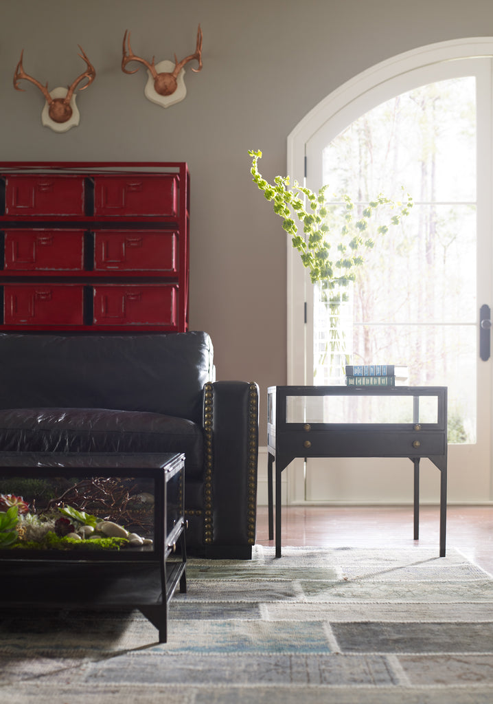 A shadowbox-inspired end table gives your inner collector a place to play. Frame prized possessions in a glass enclosure with matte-black metal and brass knobs.