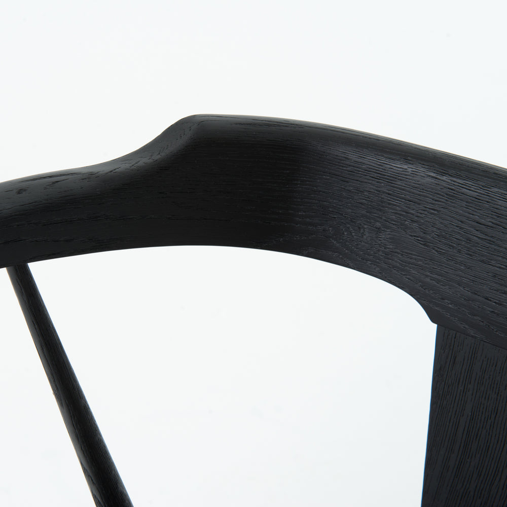 This new take on the mid-century Windsor chair has a bowed, sculptural silhouette. A soft black finish adds movement to the wood by highlighting the natural grain of weathered oak.
