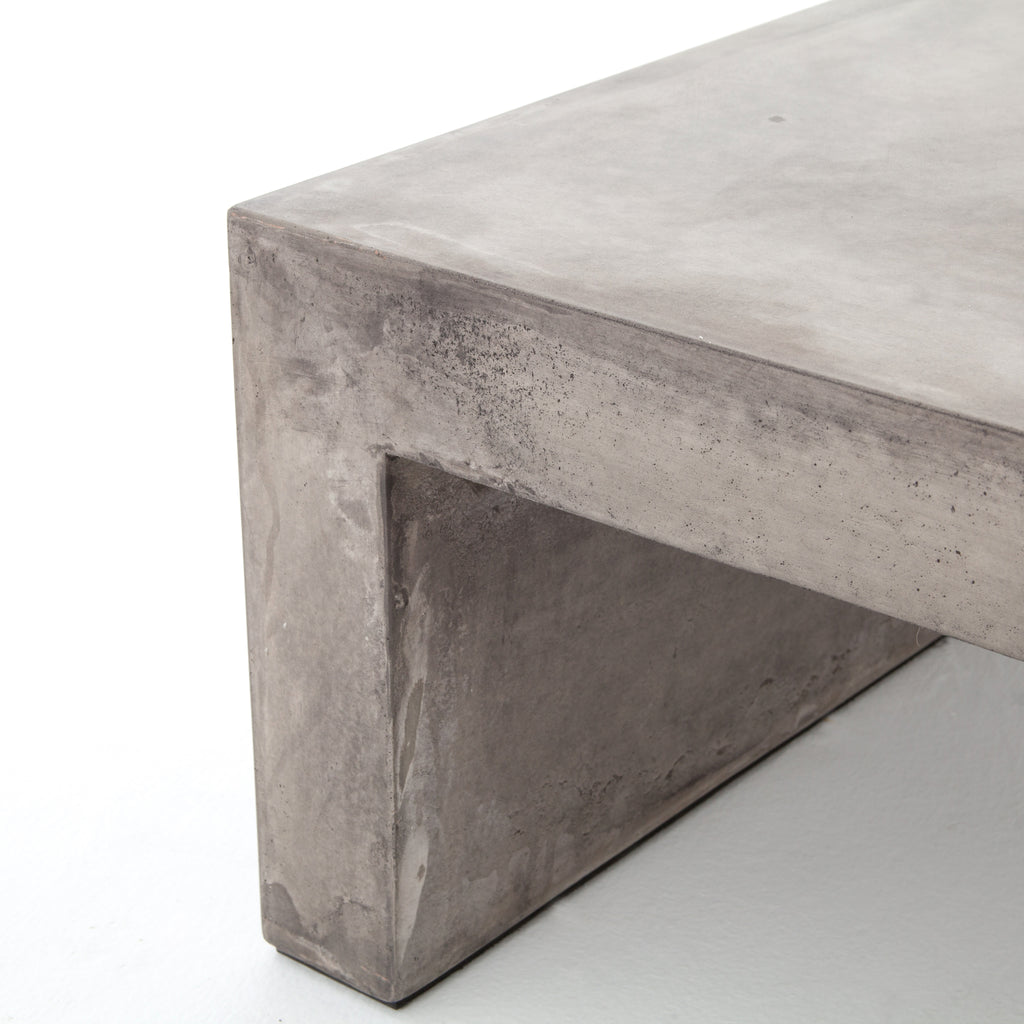 Industrial materials in smoothly refined shapes. Dark grey concrete forms a simple waterfall coffee table. Made for indoor or outdoor spaces— cover or store indoors during inclement weather and when not in use.