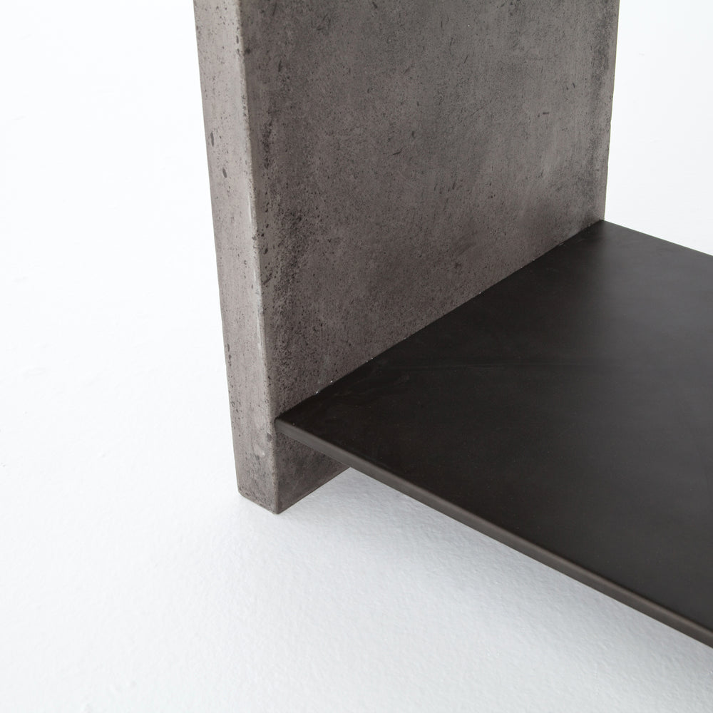 Traditionally outdoor materials are updated for indoor use. A black metal shelf seems to float between a minimalist concrete frame in dark grey, for a sleek, industrial-inspired look.