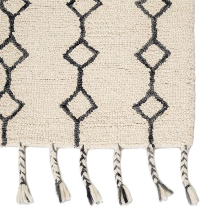 Hand-tufted of wool, the Vera collection by Nikki Chu infuses contemporary spaces with inspiring patterns and versatile colorways. The Garnet rug features a dark gray Moroccan-inspired trellis design that covers the ivory backdrop with geometric appeal. Long, braided tassels add a touch of boho-chic charm to this worldly rug.  Hand-Knotted  100% Wool VNK07 Vera Garnet Rug