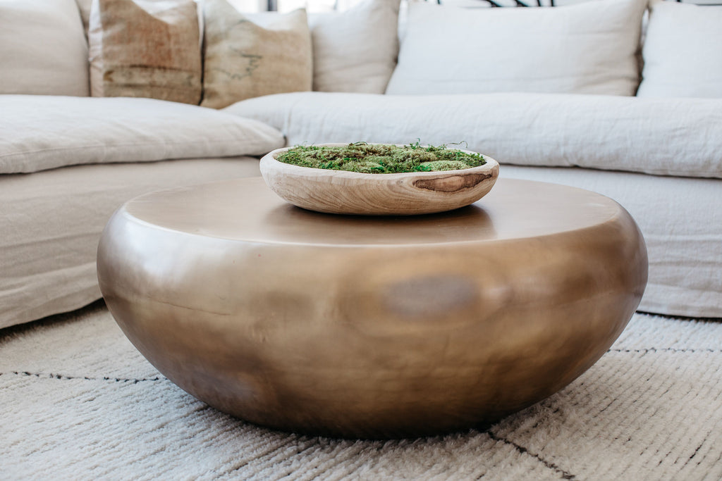 This voluminous drum cocktail table is made of iron then finished in burnt brass, a golden finish a bit lighter than antique brass. Measures 38 inches in diameter.  Burnt brass finish, iron. H: 14.5IN DIA: 38IN