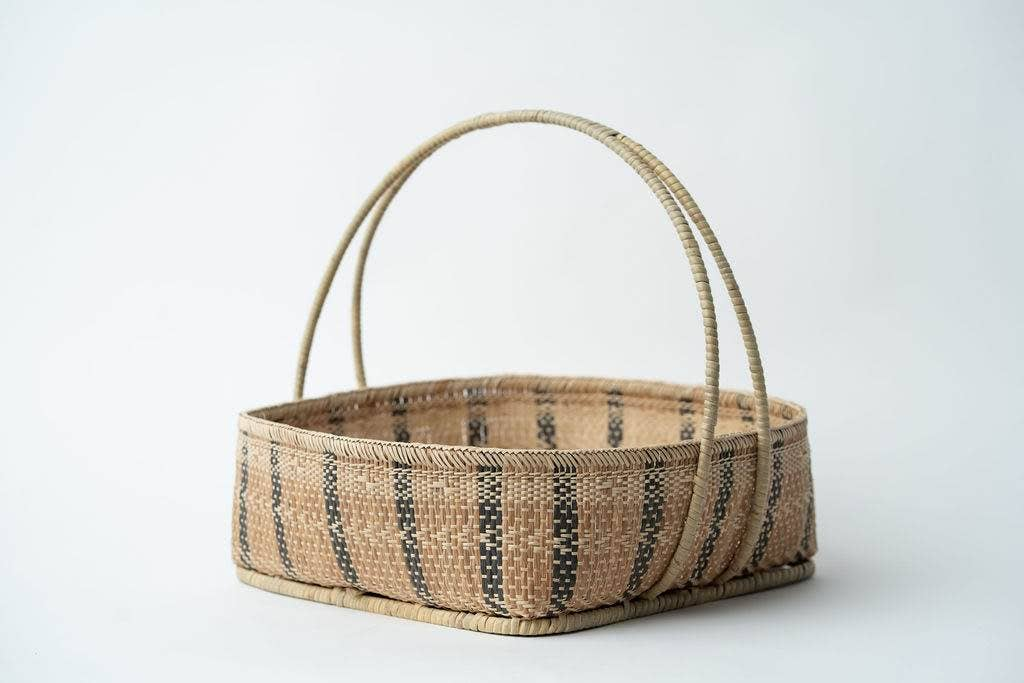 "We love how the sturdy, stylish design of the Bidayuh Basket with Handle by Neepa Hut allows ample interior space. It is the perfect balance of utilitarian and chic, making it the perfect basket to fill with wine, fruit, or other goodies.   Crafted by artisans of the indigenous Bidayuh people, each tray has a unique, intricate pattern that reflects their rich heritage. Due to the handmade nature of our pieces, there may be slight variations in size, color, and pattern  Size: 12""l x 12""w x 3.5""h"