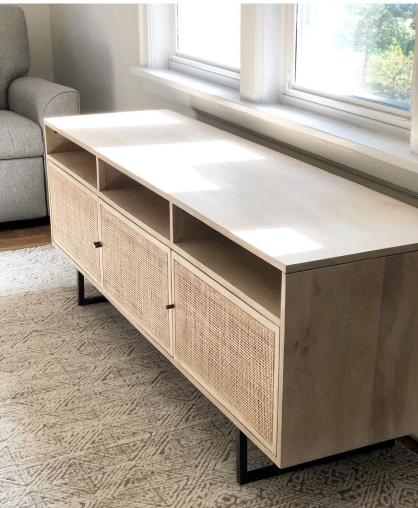 "We love the organic feel of this Carmel Natural Mango Media Console. The shelves and posterior cord management make this the perfect media console for families wanting extra storage, while also adding a mid-century look to the room.   Size: 65""w x 18""d x 24""h  Materials: Mango Wood, Cane, Iron"