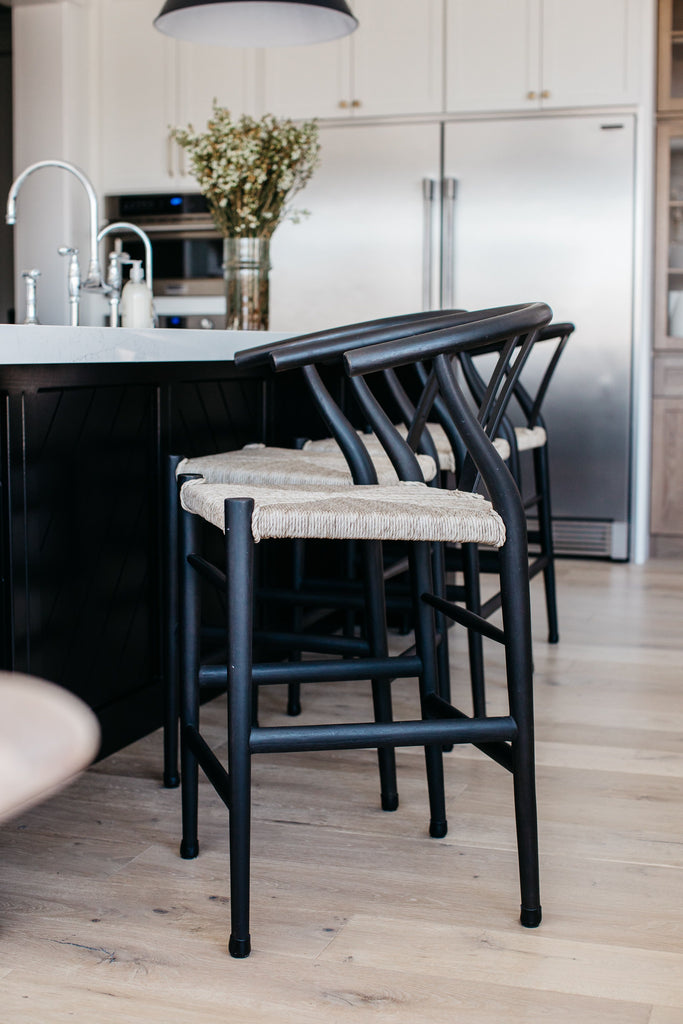Modern curves redefine the classic wishbone-style of this Muestra Black Teak Counter + Bar Stool. Vintage white all-weather wicker is woven for a dose of fresh texture within weathered grey teak framing. Cover or store indoors during inclement weather and when not in use.