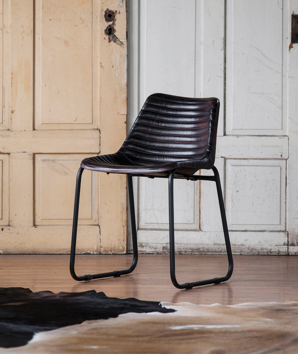 Designed for comfort and style, these mid-century modern-inspired chairs work well at a desk, or placed throughout any room for extra seating. Made of gorgeous black leather, the bucket-style seat is perfectly balanced on an elegant gun metal iron frame.