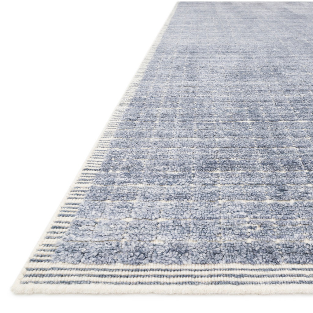 Modern and refined, the Beverly Denim rug by Loloi is hand-loomed by master artisans of viscose and wool pile. Clean lines and minimalist hues allow you to layer Beverly into any room.  Hand Loomed 68% Viscose | 32% Wool BEV-01 Denim