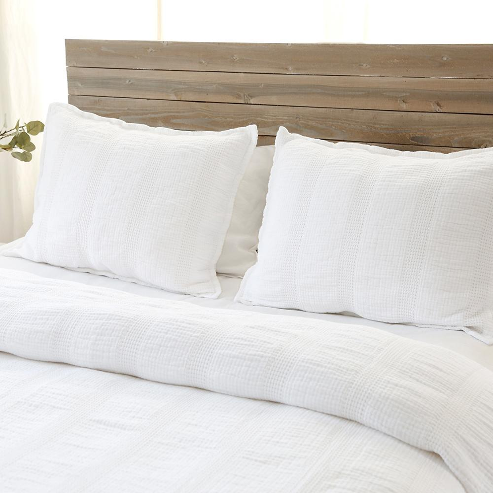 Crafted in Portugal, the Nantucket White Matelasse by Pom Pom at Home is a modern take on the matelasse with its beautiful interwoven weave. We love the soft, puckered appearance this brings to a bedroom.  Details & Care: 100% cotton. Machine wash cold; tumble dry low; warm iron as needed. Do not bleach