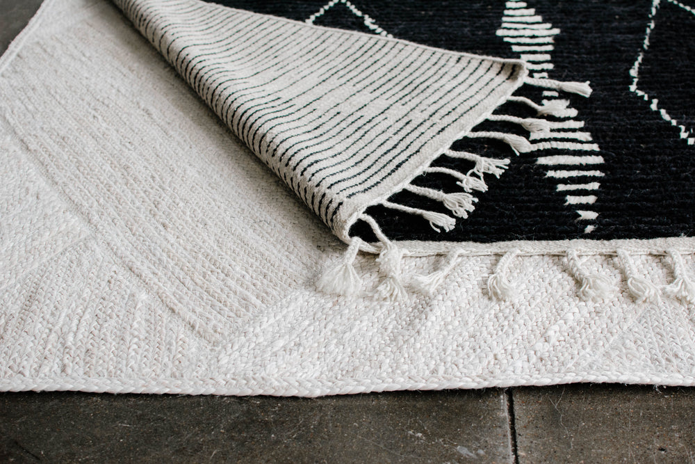 We are loving all the drama with this rug! Beautiful hand-knotted construction featuring stripes of tufted wool for an extra soft pile under foot.  Braided cotton tassels on two ends of the rug.  One-of-a-kind Moroccan Rug  100% Wool