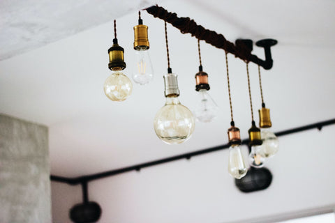 different-shaped lightbulbs hang in the ceiling of a white-colored room