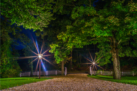 two driveway lights in a dark night welcoming passing people surrounded by trees