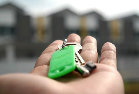 hands holding green keys pointing at a home