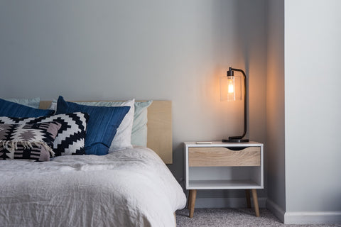 a bed and a black lamp on a nightstand