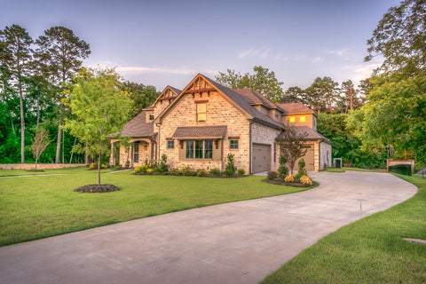 big brown house surrounded by trees with a green lawn and a big driveway