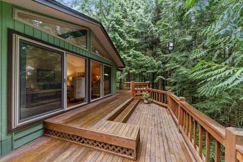 a green house with a wooden deck facing a forest