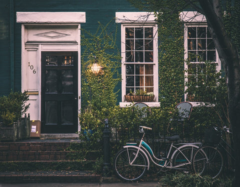 frontdoor of a house with a lamp on the side and two chairs surrounded by leafy plants nad a bike