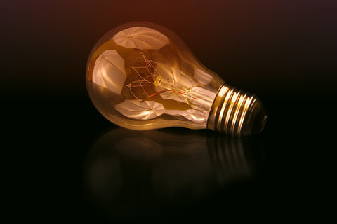 a light bulb with a reflection and a dark background