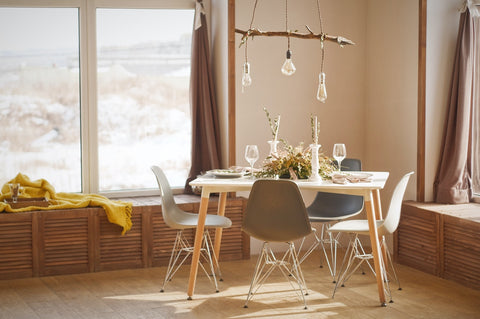 wooden dining table set with utensils and wine glass on the table and light bulbs hanging above the table