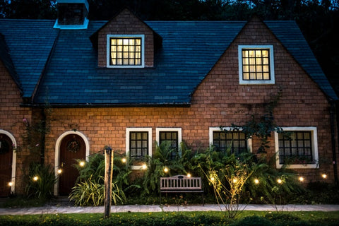 brick house beautifully decorated by hanging lights and plants