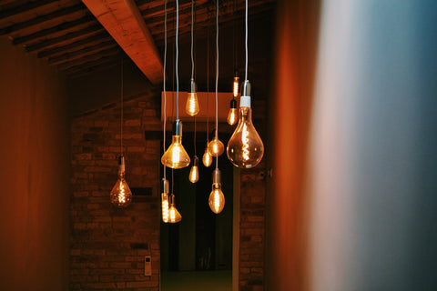 turned on pendant lamps with orange backgrounds