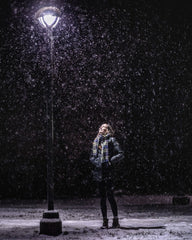 woman standing outside near a lamp post in a snowy evening