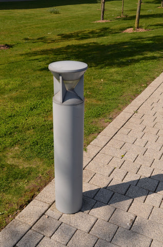 gray bollard light erected in the pathway near the grasses
