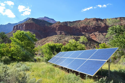 solar panels looking shined by sun and surrounded by large mountains