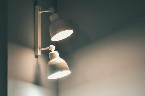 two lit up lampshades in a white wall