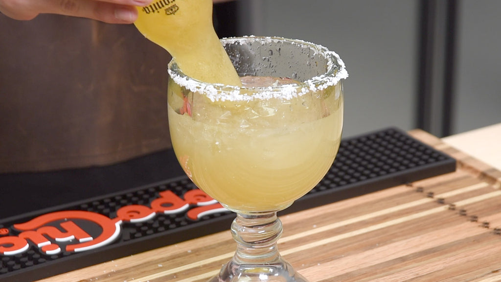 Carefully add the beer, upside down, to what is otherwise a simple margarita