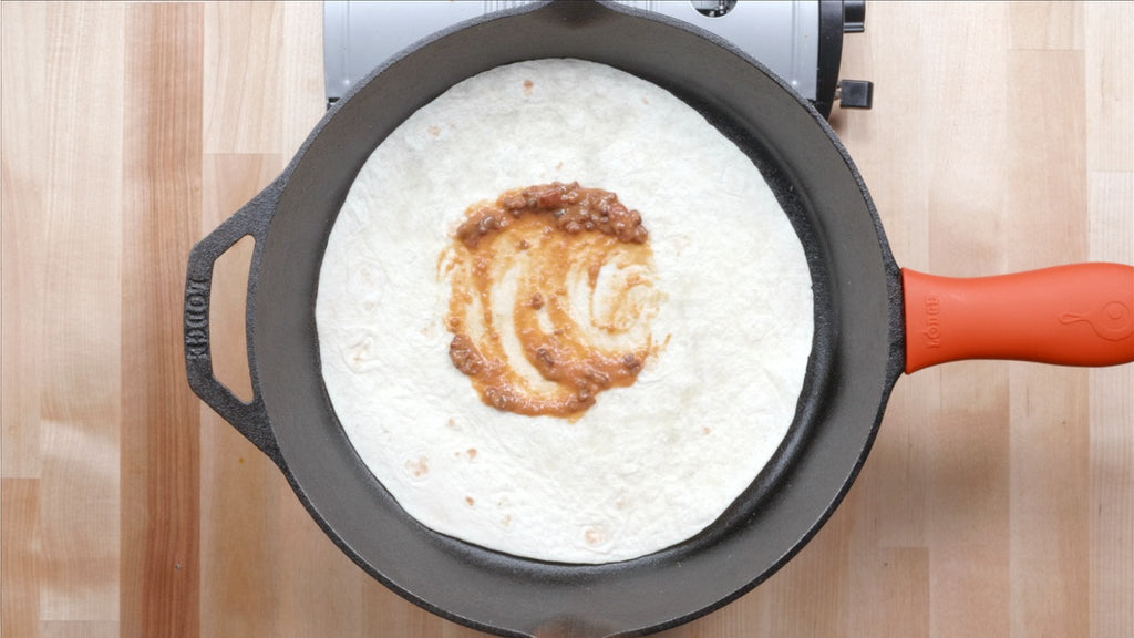 Add beans to the center of a large, burrito sized flour tortilla