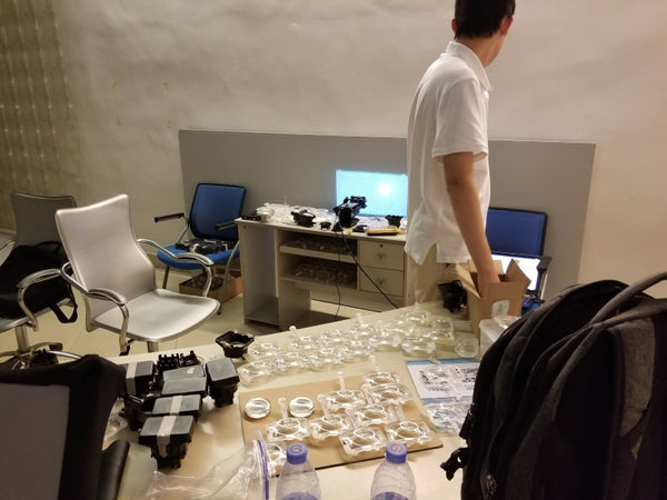 Our now-very-familiar lens testing room, with multiple lens samples, adjustable mount samples, and a testing station.