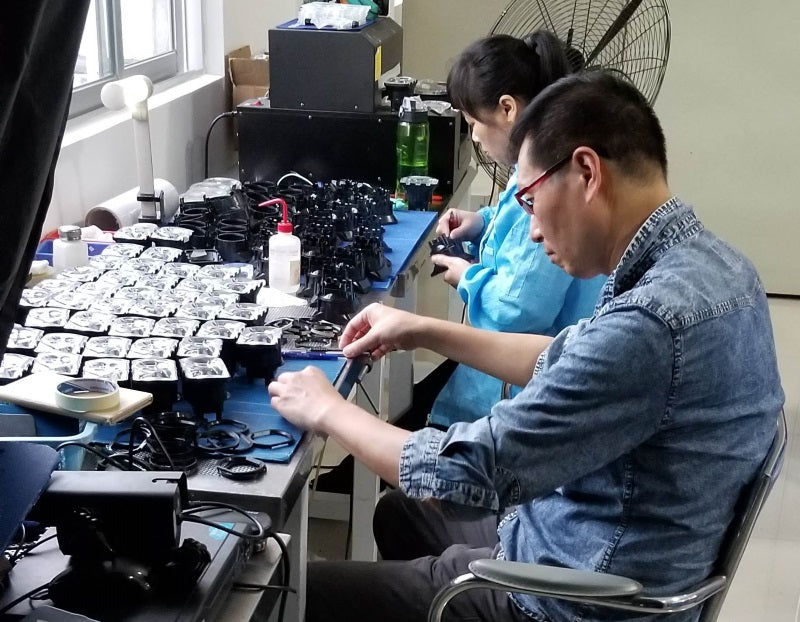 A bunch of lenses and lens assembly components on a table in the factory.