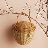 Olli Ella Acorn basket hanging on a tree branch