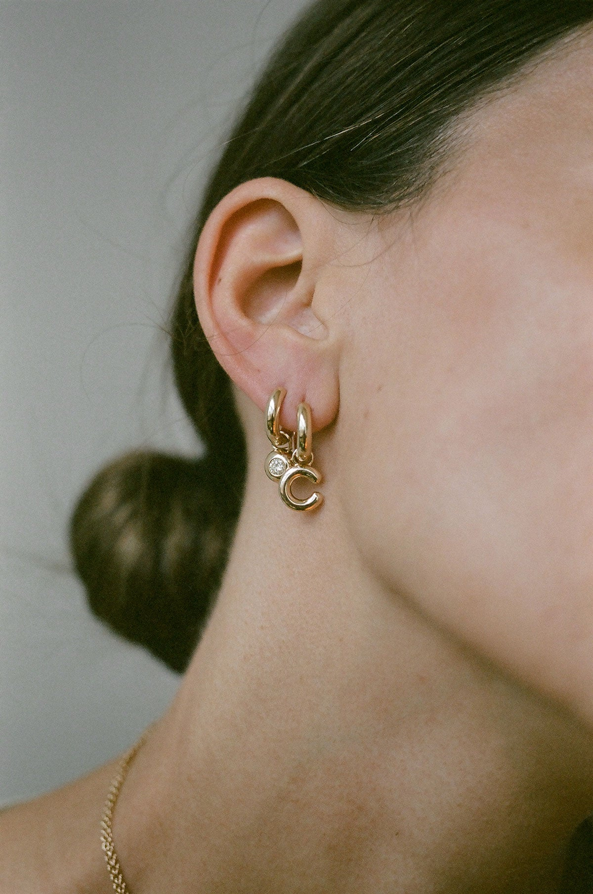 Model wearing J. Hannah Identity Charm Hoop earrings 14k gold
