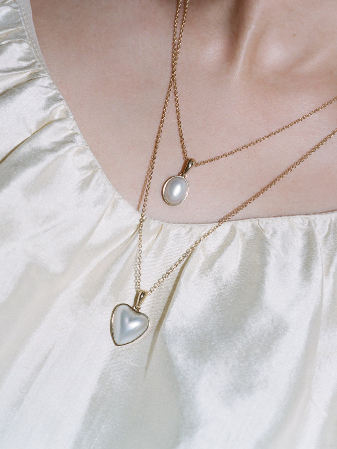 Model wearing J. Hannah Heart and Oval Mabe' Pearl Pendants 14k Gold