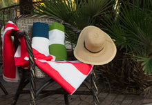 photo of large outdoor striped fabric laying on pool patio chair