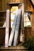 photograph of deer, antler, and forest fabric sitting on front porch of rustic cabin
