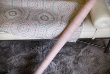 Pink and white fabric leaning on contemporary styled bench with grey rug